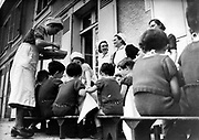Children at home run by the German Ministry of Health being served a meal outside.. World War II