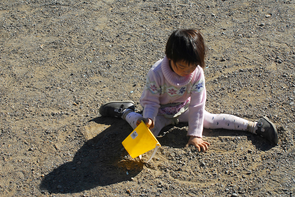 Alaska, Barrow. Iñupiat/oriental girl, Angelina Hopson plays on the yard.  July 2007