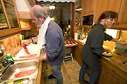 (MODEL RELEASED IMAGE). Jörg and Susanne Melander prepare rouladen, a traditional German entrée consisting of pickles, mustard, and Westphalian bacon, rolled up in a thick slice of beef, cooked, and served in rich brown gravy. (From a photographic gallery of images of kitchen images, in Hungry Planet: What the World Eats, p. 54)