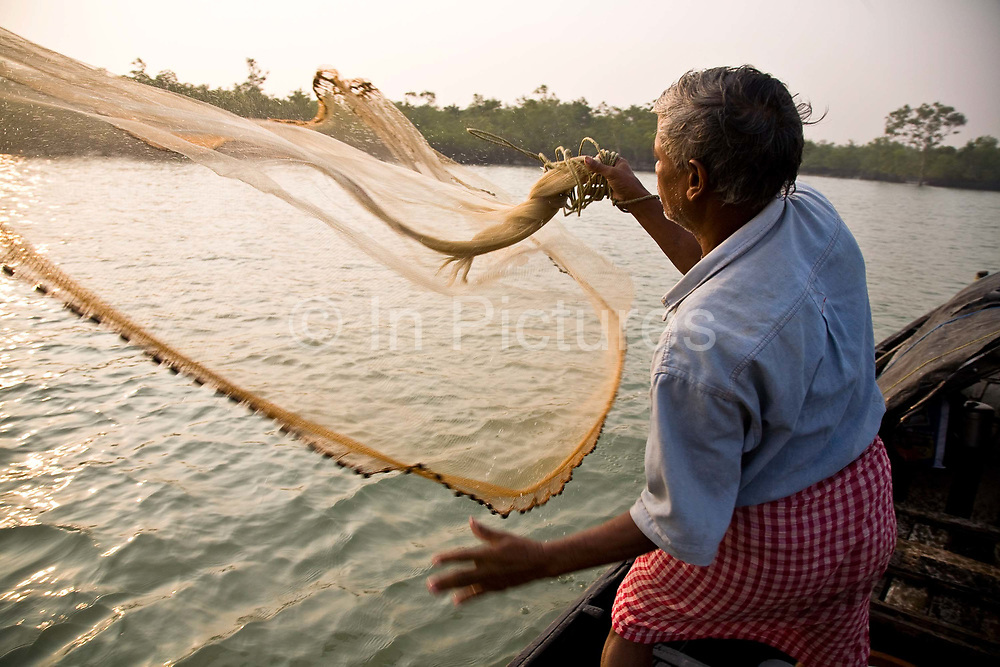 Monindro Mondol throws a large fishing net into the salt waters of the Bay of Bengal, also known as the Sunderbans delta. Most inhabitants of the delta are both fisherman and rice farmers and in the case of Monindro supplements his income by offering support services to the eco tourism business on his small island of Bali, West Bengal, India