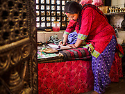 06 MARCH 2017 - KATHMANDU, NEPAL: A woman in a small Hindu shrine in Kathmandu.      PHOTO BY JACK KURTZ