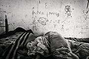 Bairro do Iraque, Iraq slum, is located in the north of Portugal. Until the late 90' this 100 persons community of gypsies lived moving from village to village working in basketry, utensils for horses and other small jobs. With the end of traditional agriculture also their traditional way of life finished.<br /> When the TV news were full of images from the second invasion of Irak, this community was expelled from the center of town moved to an old German mine of tungsten transformed in construction materials dump, abandoned in the Second World War- know now as Iraq slum.<br /> The old structures are occupied and fixed with the recycled materials from the dump. Electricity is stolen from public electric poles; light just appearing after the sun goes down in the horizon. The members of the community live from social metal scavenging, farm work, raising animals for selling and the social security check.<br /> The walls of the shelters are not enough for protecting these families from the cold and wind.