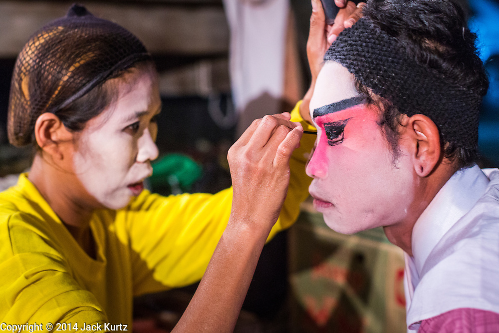 """25 JANUARY 2014 - BANG LUANG, NAKHON PATHOM, THAILAND: A performer with the Sing Tong Teochew opera troupe gets into character before a show in a Chinese shrine in the town of Bang Luang, Nakhon Pathom, Thailand. The Sing Tong Teochew opera troupe has been together for 60 years and travels through central Thailand and Bangkok performing for mostly ethnic Chinese audiences. Chinese opera was once very popular in Thailand, where it is called """"Ngiew."""" It is usually performed in the Teochew language. Millions of Chinese emigrated to Thailand (then Siam) in the 18th and 19th centuries and brought their cultural practices with them. Recently the popularity of ngiew has faded as people turn to performances of opera on DVD or movies. There are still as many 30 Chinese opera troupes left in Bangkok and its environs. They are especially busy during Chinese New Year when travel from Chinese temple to Chinese temple performing on stages they put up in streets near the temple, sometimes sleeping on hammocks they sling under their stage.     PHOTO BY JACK KURTZ"""