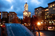 Pedestrians walk through wet streets illuminated at dusk near Pioneer Square. (Erika Schultz / The Seattle Times)