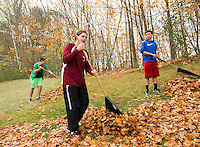 GHS Freshmen Damien Wing, Abby O'Connor and Billy McKinney rack leaves at the Gilford Community Center as part of the Gilford/Gilmanton Community Service Day on Tuesday.  (Karen Bobotas/for the Laconia Daily Sun)