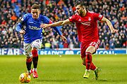 James Tavernier (C) beats Connor McLennan of Aberdeen FC during the William Hill Scottish Cup quarter final replay match between Rangers and Aberdeen at Ibrox, Glasgow, Scotland on 12 March 2019.