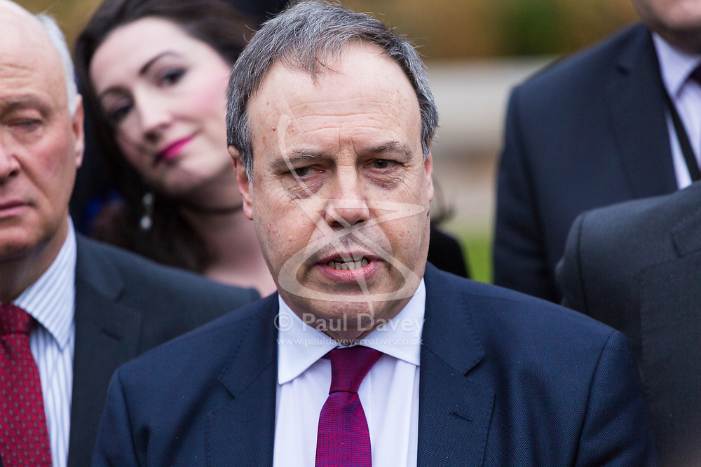 """London, December 05 2017. The DUP deputy leader Nigel Dodds flanked by other DUP MPs addresses the media, outlining the party's position relating to the Northern Ireland border in relation to the Brexit negotiations outside the House of Commons in London, as a pro EU campaigner disrupts proceedings by shouting """"Stop Brexit"""" and waving a British and an EU flag. © Paul Davey"""