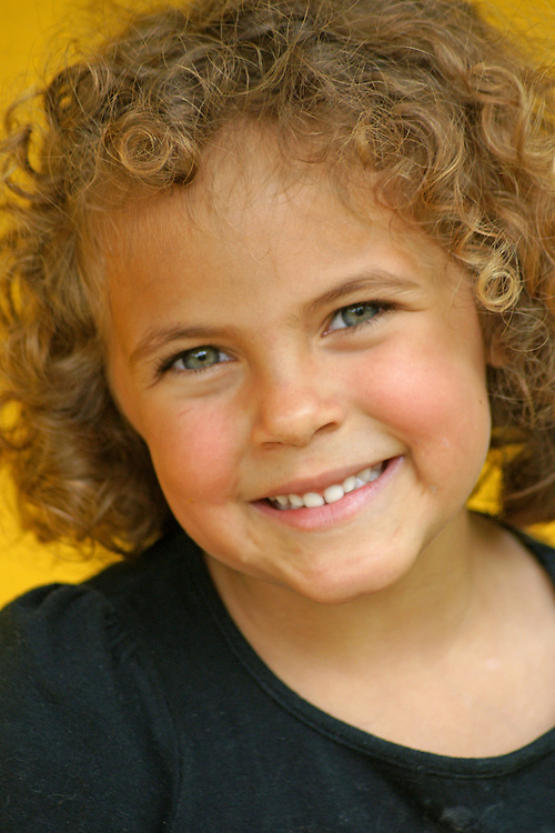 Happy girl, Janila,  with curly hair smiles in informal portrait.