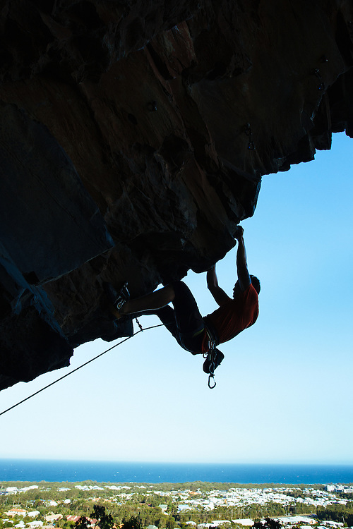 A climber is silhouetted against the background of the coastal beach and village at Mudjimba, Mt Coolum.