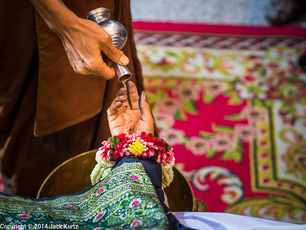 27 JANUARY 2014 - BANGKOK, THAILAND: A Buddhist monk pours water into the hand of Suthin Taratin during the bathing rites for anti-government leader at Wat Sommanat Rajavaravihara in Bangkok. In Thai tradition, after death a bathing ceremony takes place in which relatives and friends pour water over one hand of the deceased. Suthin was a core leader of the People's Democratic Force to Overthrow Thaksinism (Pefot), one of several organizations leading protests against the elected government of Thai Prime Minister Yingluck Shinawatra. He was murdered Sunday, Jan. 28, while he was leading a rally to prevent voters from reaching a polling center in the Bang Na district of Bangkok.     PHOTO BY JACK KURTZ