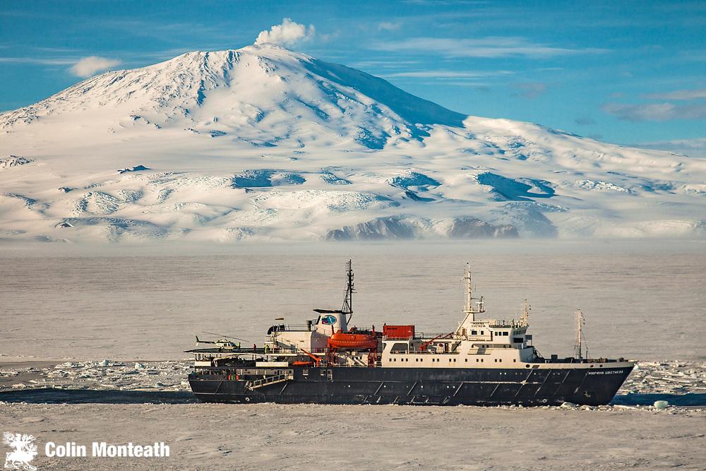 Marina Svetaeva, Ice-strengthened Russian cruise ship ( Aurora Expeditions) in McMurdo Sound sea ice - volcano Mt Erebus behind