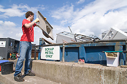 Teenaged boy recycling old kitchen sink into scrap metal skip at the city tip,