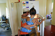 (MODEL RELEASED IMAGE). John Brown holds his sister Sinead as they graze in the nearly-empty refrigerator. Every two weeks a new check appears and the family goes to the supermarket. Hungry Planet: What the World Eats (p. 27).