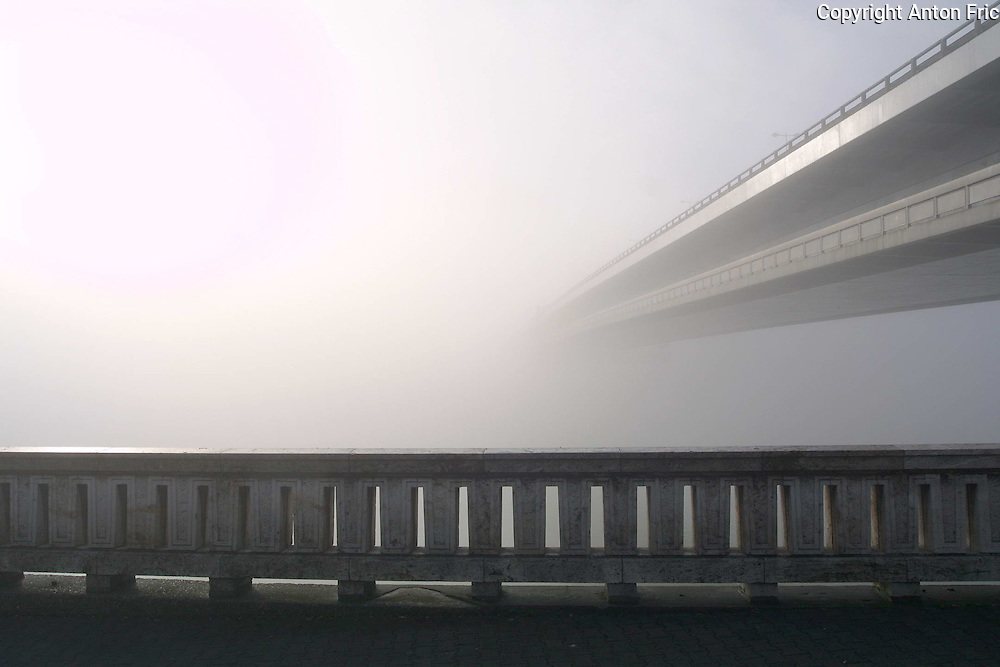 Dense fog at the Danube river banks in capital city Bratislava, Slovakia. The fog over Danube completely prevented the view on the right side of river leaving Novy most (New bridge) pointing to nowhere.
