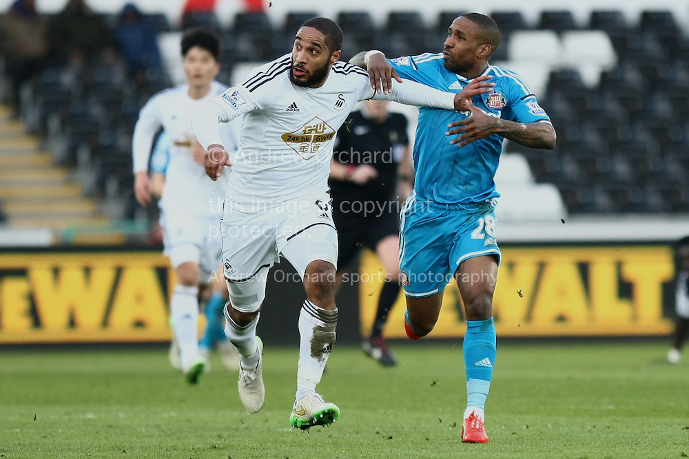 Ashley Williams of Swansea (left) grapples with Jermain Defoe of Sunderland.<br /> Barclays Premier League match, Swansea City v Sunderland at the Liberty stadium in Swansea, South Wales on Saturday 7th Feb 2015.<br /> pic by Mark Hawkins, Andrew Orchard sports photography.