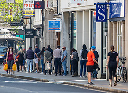 © Licensed to London News Pictures. 09/04/2020. London, UK. People queue two meters apart at shops in Richmond Town. Crowds of shoppers and people exercising come out in Richmond town ahead of the Bank Holiday weekend as Police fear Londoners won't stay at home during the lockdown and instead go out to enjoy the warm weather as Good Friday is set to be the warmest day of the year as the Coronavirus crisis continues. Photo credit: Alex Lentati/LNP
