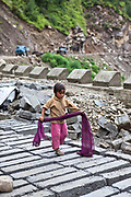 A young girl left to play on the side of the road, the child belongs to the Migrant community working on surfacing a road in the Central Himalayas, India.  The migrant community is offered education and information support by the Pragya organization that have a project helping in high altitude areas across the Himalayas.