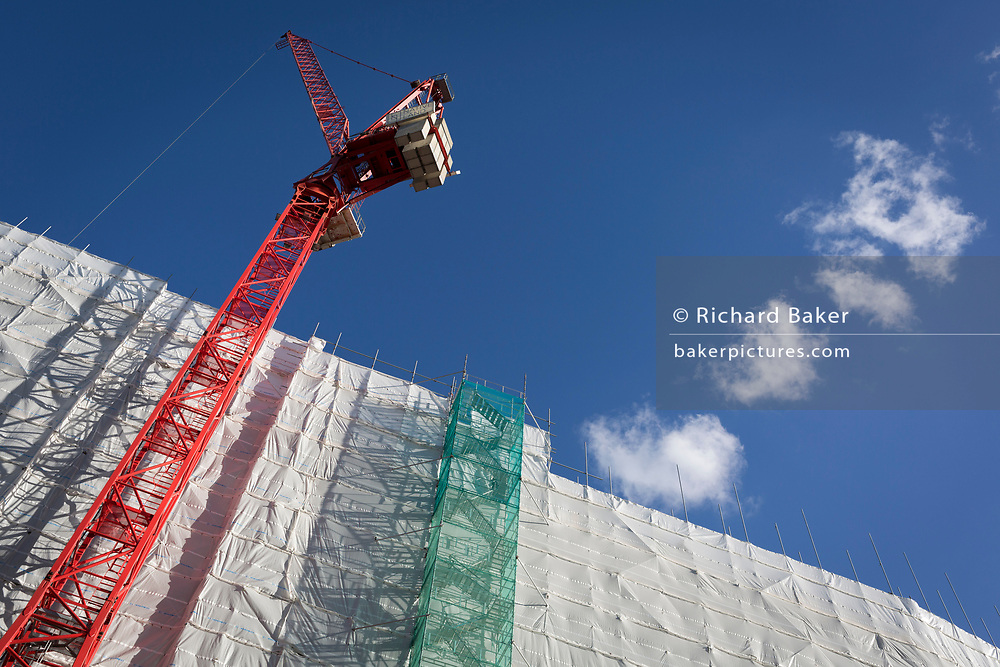 Construction and a tall gantry tower tied to the side of an office building (formerly Express Newspapers) being renovated at the southern end of Blackfriars Bridge, on 27th October 2017, in London, England.