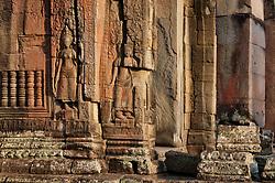 Two gandharvas seen carved in walls of Banteay Kdei in sunset, deep reddish-orange hues