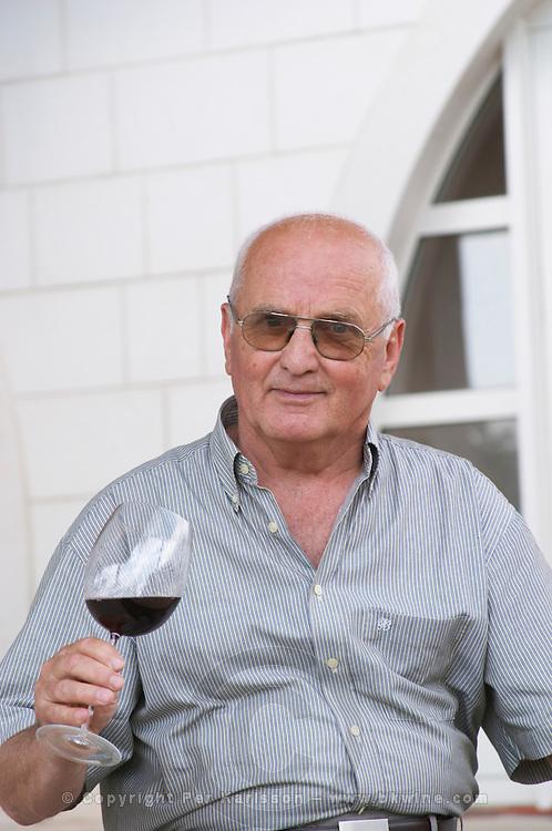 Veselko Sivric, owner and wine maker, outside his winery with a glass of wine. Podrum Vinoteka Sivric winery, Citluk, near Mostar. Federation Bosne i Hercegovine. Bosnia Herzegovina, Europe.