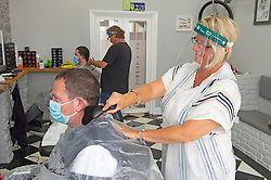©Licensed to London News Pictures 04/07/2020     <br /> Petts Wood, UK. A hairdresser working with a face shield on. Mr Snips hair studio and Barber shop in Petts Wood high street, Petts Wood, South East London, has reopened today after three months of coronavirus lockdown. Staff and customers have to wear PPE. Photo credit: Grant Falvey/LNP