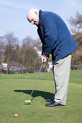 Older man playing pitch and put,