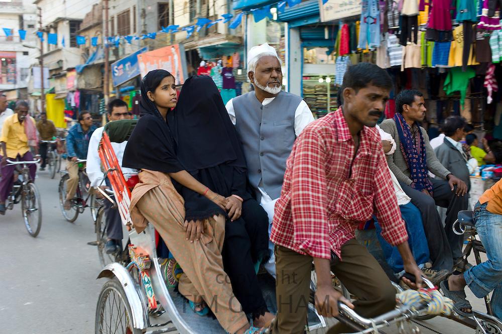 Street scene in holy city of Varanasi, muslim family ride in rickshaw, Benares, Northern India
