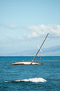 A sailboat sits off the shore of Maui stuck on a reef.