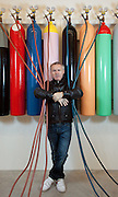 """Damien Hirst portrait with his artwork.""""Greetings from the Gutter/ Avoiding the Inevitable"""".1994.Glass, steel, gas cylinders, rubber, acrylic, MDF, gas mask, saline bags and needle.Dimensions variable.© Damien Hirst. All rights reserved, DACS 2010.Photographed in his Chalford Studio, near Stroud, Gloucestershire"""