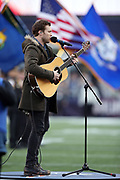 Phillip Phillips sings plays the guitar and sings the National Anthem before the New England Patriots AFC Championship NFL playoff football game against the Jacksonville Jaguars Patriots, Sunday, Jan. 21, 2018 in Foxborough, Mass. The Patriots won the game 24-20. (©Paul Anthony Spinelli)