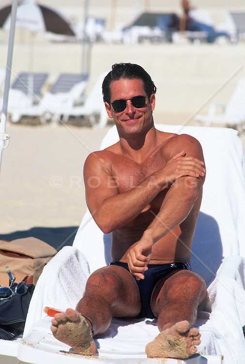 Handsome man on a lounge chair at the beach putting on lotion