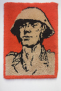 A soldier image on a rug, an exhibit in 'Haus 1' the ministerial headquarters of the Stasi secret police in Communist East Germany, the GDR. Built in 1960, the complex now known as the Stasi Museum. Before the fall of the Wall, it was a 22-hectare complex of espionage whose centrepiece is the office and working quarters of the former Minister of State Security, Erich Mielke who considered their role as the 'shield and sword of the party', conducting one of the world's most efficient spying operations against its political dissenters during its 40-year old socialist history. During Hitler's Third Reich, the Gestapo had one agent for every 2,000 citizens whereas the Stasi had approximately an spy for every 6.5. Here at the Stasi HQ alone 15,000 were employed plus the many regional stations. German media called East Germany 'the most perfected surveillance state of all time' - administered from this complex of offices.