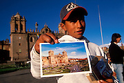 PERU, HIGHLANDS, CUZCO Plaza de Armas; boy with postcards