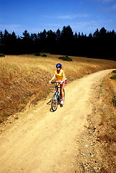 California: Marin County.  Woman biking on Dipsea Trail in Muir Woods.  Model Released..Photo copyright Lee Foster, 510/549-2202, lee@fostertravel.com, www.fostertravel.com..Photo # camari104