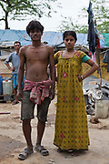 An Indian husband and wife stand together in their family compound in Tehkhand Slum, Delhi , India.  Their family survives from earning a living by recycling old industrial waste, such as scrap metals.
