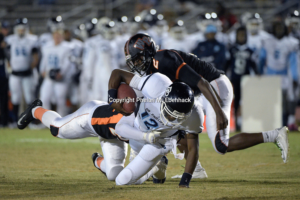 Dr. Phillips quarterback Randolph Norwood (12) dives after scrambling for yardage between Winter Park linebacker Austin Kneeland, left, and Malik Chatman (2) during the first half of a high school football game in Winter Park, Fla., Friday, Nov. 7, 2014. (Photo by Phelan M. Ebenhack)