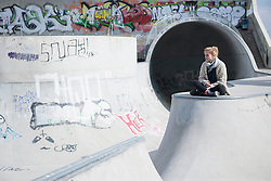 Young woman sitting in skateboard park, Munich, Bavaria, Germany