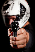 Man with motorbike helmet holds hand gun pointed at viewer - model rellease available