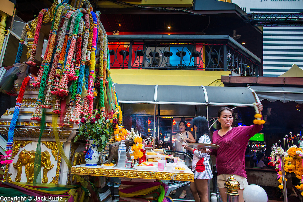 """21 JANUARY 2013 - BANGKOK, THAILAND:  Workers in the Nana Entertainment Plaza, a red light district in Bangkok, pray and make offerings at a shrine at the entrance to the plaza. Prostitution in Thailand is technically illegal, although in practice it is tolerated and partly regulated. Prostitution is practiced openly throughout the country. The number of prostitutes is difficult to determine, estimates vary widely. Since the Vietnam War, Thailand has gained international notoriety among travelers from many countries as a sex tourism destination. One estimate published in 2003 placed the trade at US$ 4.3 billion per year or about three percent of the Thai economy. It has been suggested that at least 10% of tourist dollars may be spent on the sex trade. According to a 2001 report by the World Health Organisation: """"There are between 150,000 and 200,000 sex workers (in Thailand).""""  PHOTO BY JACK KURTZ"""