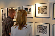 Young couple looking at a photography exhibit display at Studios On The Park,  Art Studios & Galleries, Paso Robles, San Luis Obispo County, California