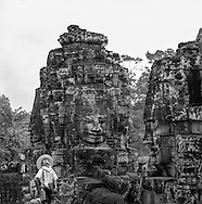 Tourist looks up at the massive stone faces surrounding him, Bayon temple, <br /> Angkor, Siem Reap, Cambodia, 2005, Southeast Asia