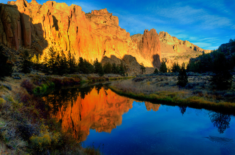 The cliffs at Smith Rock art turned red by the setting sun, and are reflected in the blue waters of the river.