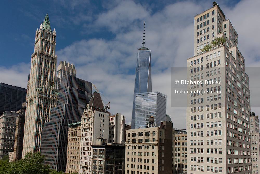 Wide cityscape of skyscrapers looking across Broadway to the modern WTC center in Manhattan, New York City.