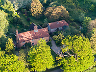 A large cottage in the Suffolk countryside in England during the summer with green trees