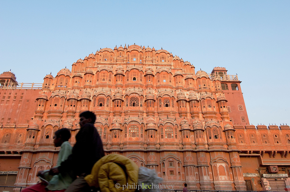 Locals passing the Hawa Mahal, the Palace of Winds, in Jaipur, India