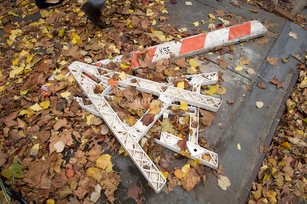 fallen over sawhorse on the sidewalk with autumn leaves