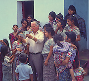 Catholic priest showing villagers some photos, Santiago Atitlan village, Guatemala, central America,