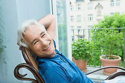 Portrait of mature man sitting in rocking chair, smiling
