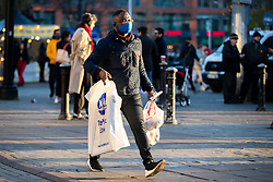 © Licensed to London News Pictures. 05/12/2020. Manchester, UK. A shoppers carries his bags down a busy Market Street in Manchester as people try to fit in Christmas shopping. Non-essential retail is open in Manchester which is in Tier 3 restrictions. Photo credit: Kerry Elsworth/LNP