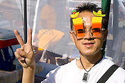 Hmong man age 21 wears island sun glasses gives peace symbol. Hmong Sports Festival McMurray Field St Paul Minnesota USA
